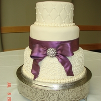 Three-Tier Wedding With Purple Bow. Ivory fondant with fondant bow.