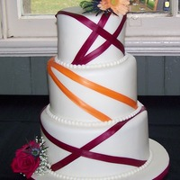 Fuchsia And Tangerine Ribbon Wedding Cake.  Marshmallow fondant covered 3-tiered wedding cake with fuchsia and tangerine ribbon and fondant pearls. The cake is a traditional white...
