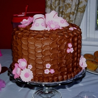 Baby Girl Shower Cake Chocolate butter cream cake done with the petal effect. Baby booties and flowers are gum paste.