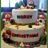 Merry Christmas Two tiers with alternating layers of WASC and chocolate WASC. Chocolate BC filling, frosted with white chocolate SMBC, covered with MMF....