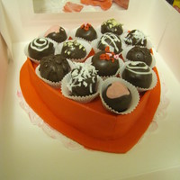 Box Of Chocolate Cake Red velvet cake covered with red fondant and chocolate dipped cake balls decorated like chocolates