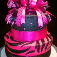 Hot Pink And Black Zebra Print Hot pink and black zebra print cake. Buttercream with fondant zebra stripes. Cake accesorized with ribbon.