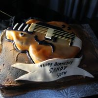 Guitar Cake A replica of a client's guitar....hollow body electric! I used spaghetti sticks as the strings...I carved out the guitar from cake and...