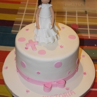 Girl - Holy Communion This communion cake has a handmade girl holding a white purse. The design includes a simple pink cross with pink mini flowers and dots. The...