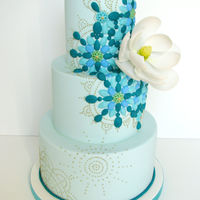 Turquoise Mosaic Cake A gumpaste magnolia is set against a bejeweled mosaic backdrop in turquoise, blue and green. Flavour is spiced carrot cake with cream...