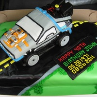 Back To The Future 1/2 + 1/2 choc and vanilla sheet with the car carved out of Madera cake