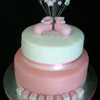 Christening/baby Shower Bootees 2 tier cake with sugarpaste boottees and flower spray to finish it off