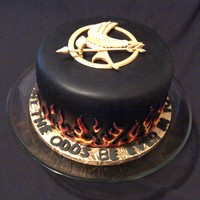 "Hunger Games Chocolate fondant covered 8"" with red velvet cake and cream cheese filling. Handcut gumpaste mocking jay and piped flames. For our..."