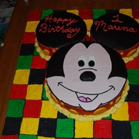 "Mickey Mouse Cake The cake board is 27x35 color blocked in royal icing. The head is a double layer 14"" round and the ears are double layer 10'..."