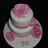 Beautiful 40 Two tiered, fondant covered cake in pink and white with pink gumpaste roses with rhinestone centers.