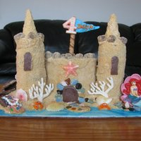 Sand Castle Cake sand castle cake. towers are stacked cupcakes. white and dark chocolate decorations. castle is covered with buttercream and vanilla cookie...