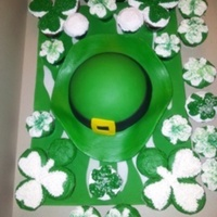 St. Patricks Darby Cake Covered with green fondant, Irishman darby, and white buttercream iced cupcake with green sprinkles.