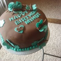 Almond Joy Cake In Fondant An almond joy cake covered in brown fondant and decorated with teal accents.