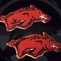 Razorback Sugar Cookies Sugar cookie iced with royal icing in red. I then painted each hog on with black food coloring gel.