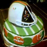 University Of Miami Groom's Cake Cake is buttercream with fondant circles and royal icing accents. Helmet is RKT and fondant.