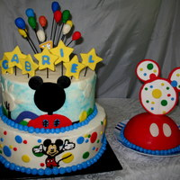 Mickey Mouse Birthday Cake Cake is covered in buttercream with fondant and gumpaste decorations.