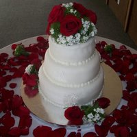 Floral Wedding Cake Fondant Wedding Cake with White Royal Icing Decoration and Live Roses.