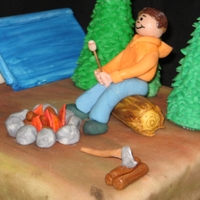 Camping Cake This is a camping cake for a friend's son. I made a little gumpaste figure sitting on a log roasting a marshmallow over a campfire....