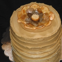 Southern Caramel Cake Vanilla buttermilk cake filled and iced with a cooked caramel frosting. Gumpaste fantasy flower tops it off.