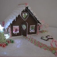 Gingerbread House For My Children Gingerbread house with people decorating tree and making snow angels. People inside were hanging decorations and opening presents.
