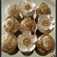 Rococo Cupcakes A collection of elaborate Rococo inspired gold and ivory fondant wedding cupcakes with edible sugar brooches & flowers hand painted...