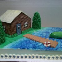 Lake Cabin Bottom is vanilla cake. Cabin, trees and boat are rice krispy treats covered in buttercream and fondant. Pier is cake covered in...