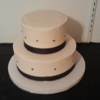 Simple And Elegant This was a quick last minute order. They wanted something simple and elegant. A two tier round with chocolate ribbon around the bottom for...