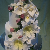 Cherie A 2 tier wedding cake decorated with sugar lillies and rosebuds