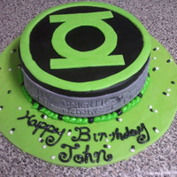 "Green Lantern This is a confetti cake with fondant. On the front side of the cake there is a ""marbleized"" plaque that reads the first two lines..."
