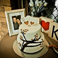 Robert & Kirsten's Engagement Cake 2 teir engagement cake coverd in fondant, free hand cut tree, and hand painted cake topper - the ring was also made to replicate the real...