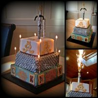 Medieval Themed Sponge Cake With Fireworks 3 tier stacked sponge decorated in a medieval theme. Edible photo images and modelling paste jewelled sword