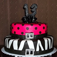 Punky Gothic Cake Two tiered chocolate stout cake filled with chocolate ganache. Zebra stripes and polka dots with a black 13 and black roses.