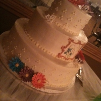 Gerber Daisy And Butterfly Wedding Cake This is a cake I made for a wedding. The flowers and butterflies are made from gumpaste. The monogram is hand piped and painted. The top...