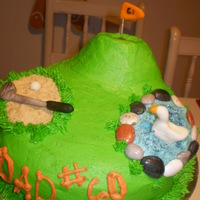Golf Cake  round sponge cake with buttercream frosting.. rocks are edible, duck and gold club are gumpaste. used donuts for the hill with hole in one...