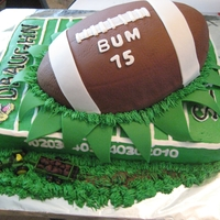 Football Field Farm Tractor Cake  Football exploding into football field with a little toy John Deere Tractor pulling a manure spreader in the grass along the front edge of...