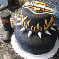 Harley Style Tire Spiked Collar Flames Birthday Cake Tiered cake with Harley Style Logo in Top Tire on the Bottom Spiked Collar and Flames on the sides top layer was orange flavored cake...