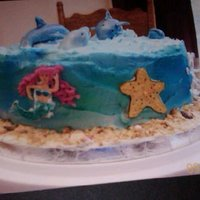 "Dolphin Cake I made the dolphins and side decorations of gum paste, used my angled spatula to create ""waves"", used spray color to control the..."