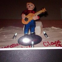 "Guitar Shaped Cake With Gum Paste Figurine This is a graduation cake shaped like a guitar. Sitting in the ""hole"" is a figurine of the grad playing his acoustic guitar. The..."