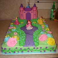 Birthday Cakes Simple princess cake; Disney Princess DecoPac, royal icing flowers, buttercream bushes and top of cake, fondant walkway dyed purple, then...