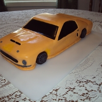 Ford Mustang 3-D car from scratch yellow cake - crumb coated in buttercream & covered in yellow fondant w/fondant details.