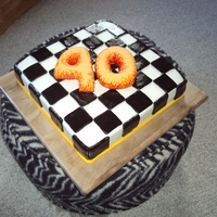 Checkerboard Racing Cake Carrot cake with cream cheese frosting, decorated with fondant. 40 made out of crispy treats. Flames painted with vodka diluted gel colors...