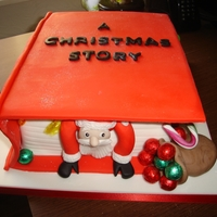 A Christmas Story vanilla sponge with raserry jam and vanilla buttercream ; santa and an elf climbing out off the book