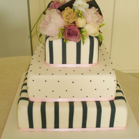 Dots And Stripes Themed Wedding Cake With Fresh Flowers This elegant Ivory, pink and black, Three tiered Wedding cake has a dots and stripes theme topped with a fresh flower arrangement.www....
