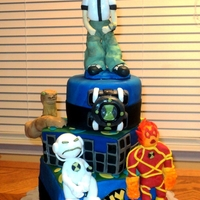 Ben-10 Cake cake made for a 6 year old boys birthday. layers are chocolate and vanilla with vanilla buttercream. Design is a city scape at night with...