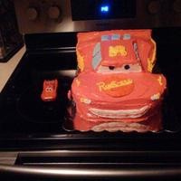 Lighting Mcqueen This was done with some buttercream and then also store bought strawberry icing it was completely carved from two half sheet white cakes...