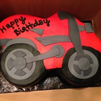 Red Motorcycle 11X15 shaped as motorcycle covered in smoothed buttercream with fondant accents.