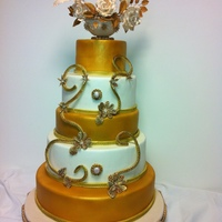 Wedding Cake In Gold All five tears cover in fondant airbrushed with gold and pearl sheen, gum paste flowers in gum paste urn decorated with piped royal icing...
