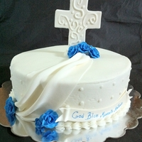 Bautizo buttercream covered in satin ice fondantcross and flowers made of gumpaste