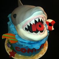 "Shark Birthday Cake With Matching Cupcakes 6' cake with matching cupcakes. Shark is RKT covered in fondant. All other decorations are fondant. ""Sand"" is crushed graham..."