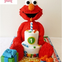 3D Elmo Carved Elmo Cake with a small tiered cake and a cake gift! head, legs & arms made of RKT all covered in fondant with fondant details....